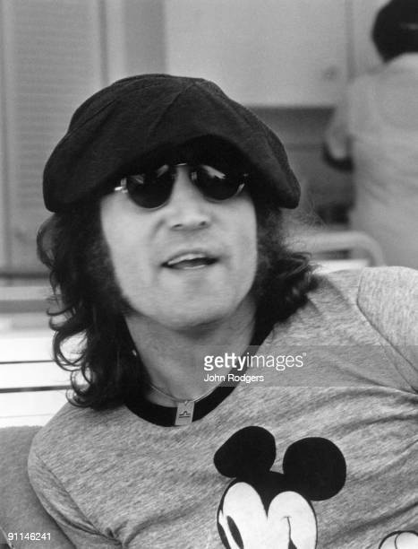 Photo of John LENNON posed wearing Mickey Mouse tshirt