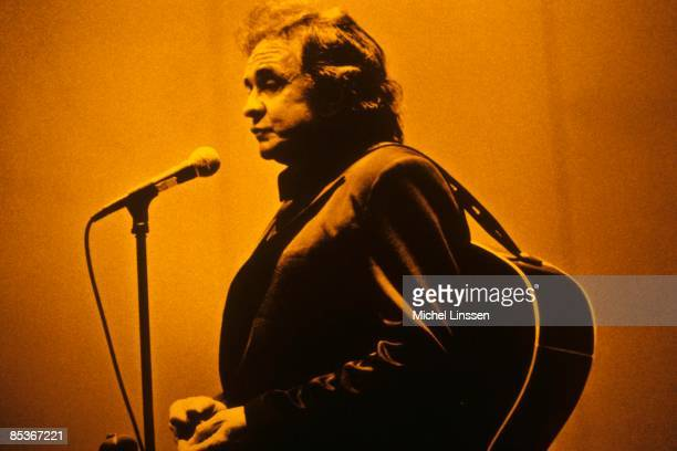 Photo of Johnny CASH Johnny Cash performing on stage acoustic guitar behind back