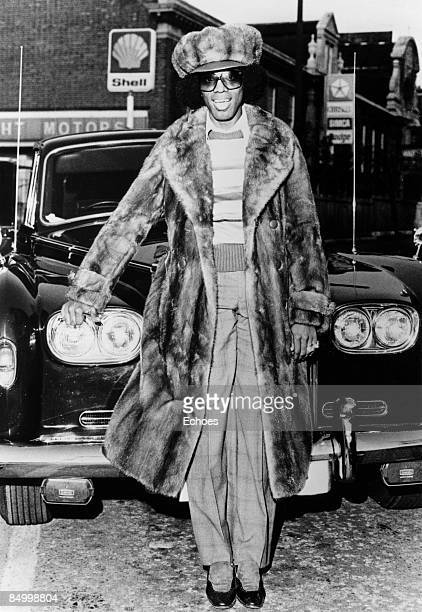 Photo of Johnny Guitar WATSON Posed full length portrait of Johnny 'Guitar' Watson standing in front of a car wearing fur hat and long fur coat and...