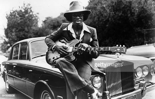 Photo of Johnny Guitar WATSON Posed portrait of Johnny 'Guitar' Watson sat on car bonnett with guitar wearing hat and sunglasses