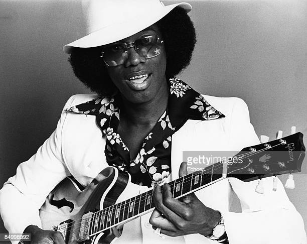 Photo of Johnny Guitar WATSON Posed studio portrait of Johnny 'Guitar' Watson with a guitar wearing white suit and hat