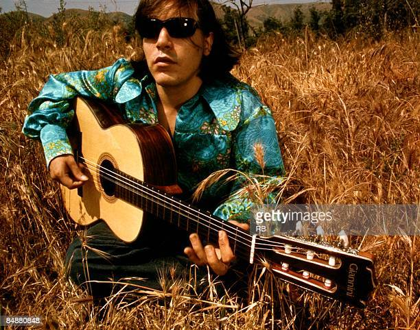 Photo of Jose FELICIANO Posed portrait of Jose Feliciano with a guitar in a field