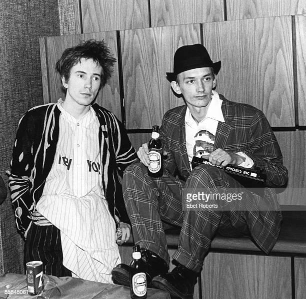 Photo of Keith LEVENE and PIL and John LYDON and PUBLIC IMAGE LTD LR John Lydon Keith Levene holding bottles of Heineken beer