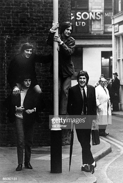 Photo of KINKS and Mick AVORY and Pete QUAIFE and Dave DAVIES and Ray DAVIES Posed group portrait in the streets of Soho lamp post LR Pete Quaife...