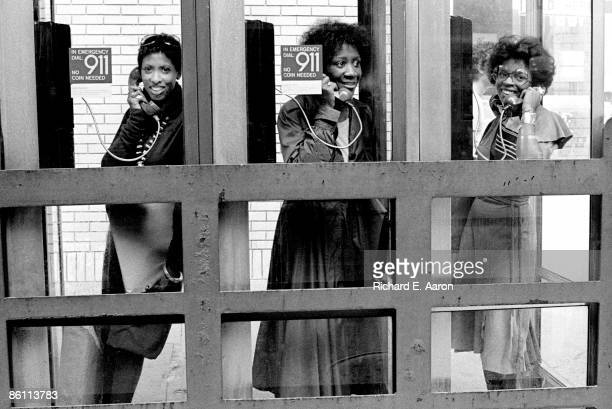Photo of LABELLE and Nona HENDRYX and Patti LABELLE and Sarah DASH Group portrait in telephone box LR Nona Hendryx Patti Labelle and Sarah Dash