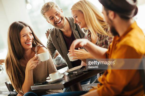 Photo of laughing friends having coffee in cafe together