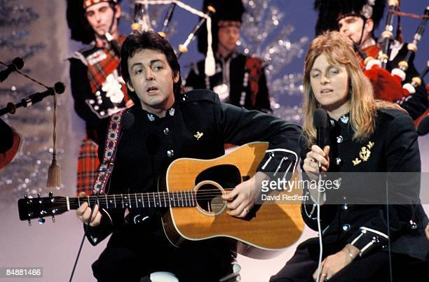CENTRE Photo of Linda McCARTNEY and Paul McCARTNEY and WINGS with Linda McCartney in Wings performing on TV show playing acoustic guitar with bagpipe...