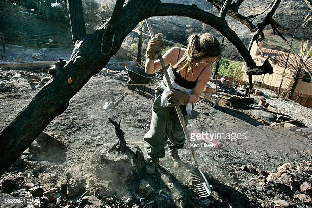 Photo of Lisa Briggs of Topanga helping out clearing debris of burned out home on Seabreeze Drive in Corral Canyon Thursday afternoon, December 13,...