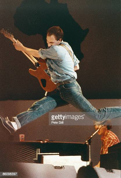 Photo of LIVE AID and Pete TOWNSHEND and The Who Pete Townshend performing live onstage at Live Aid jumping in air
