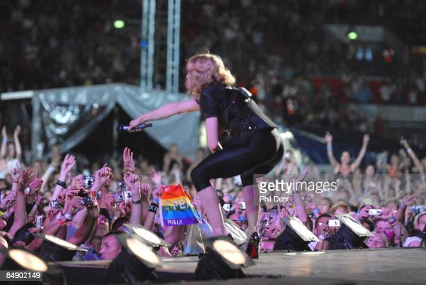 STADIUM Photo of MADONNA Madonna performing live on stage at the Live Earth Concert Crouched down holding mic to crowd