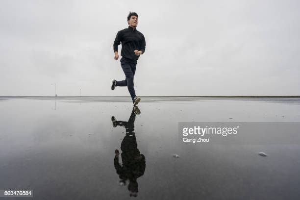 photo of male athlete running through puddle against cloudy sky