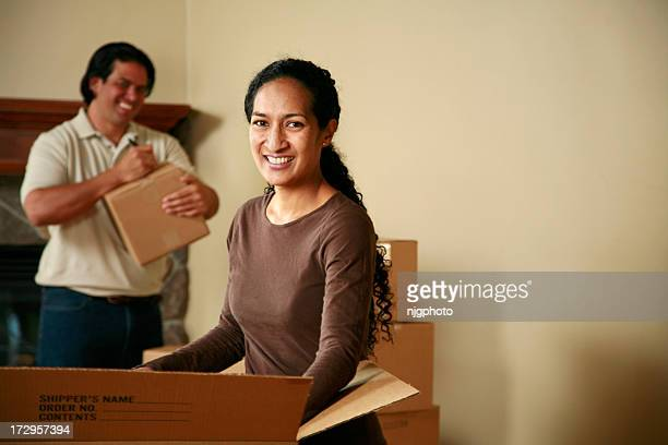 Photo of man and woman unpacking brown boxes on moving day