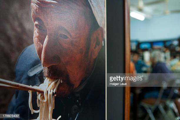 Photo of man eating noodles at restaurant