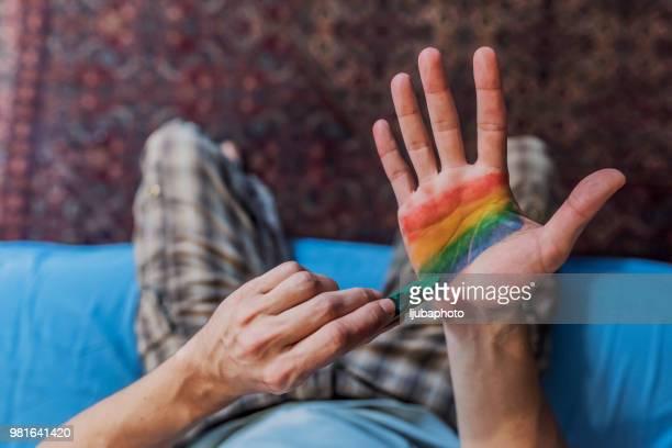 色付きのフラグを手に塗る男の写真 - レインボーフラッグ ストックフォトと画像
