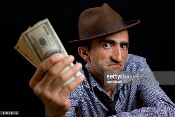 photo of man with fedora hat holding dollar bills - con man stock pictures, royalty-free photos & images