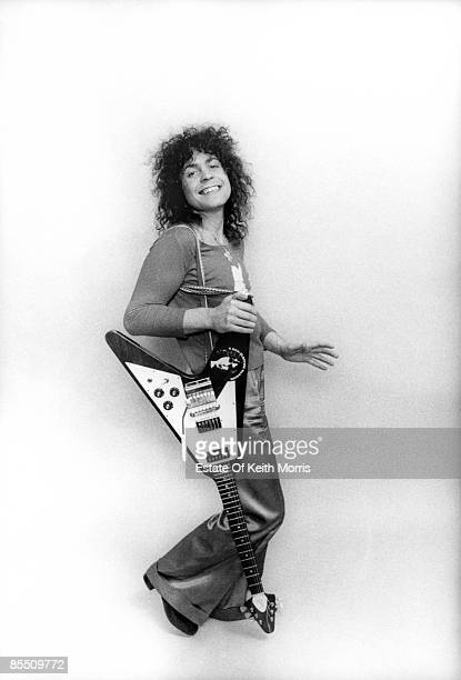 Photo of Marc BOLAN and T REX; posed, studio, with Gibson Flying V guitar