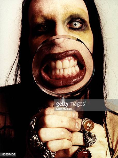 Photo of MARILYN MANSON Posed studio portrait of Marilyn Manson with magnifying glass over mouth