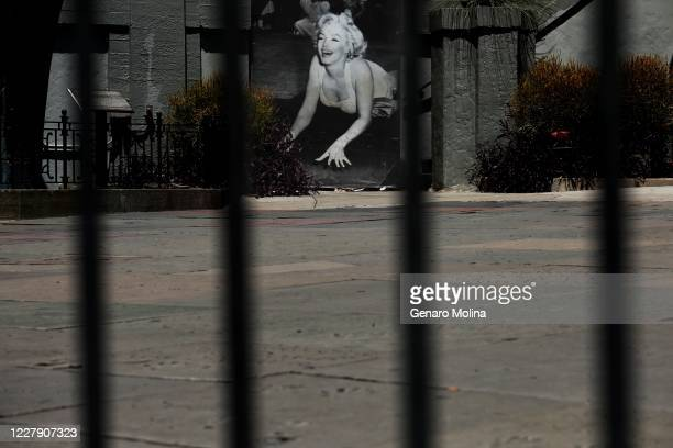 HOLLYWOOD CA JULY 28 2020 A photo of Marilyn Monroe and the famed hand and footprints of actors at the TCL Chinese Theatre rest behind a barricade in...