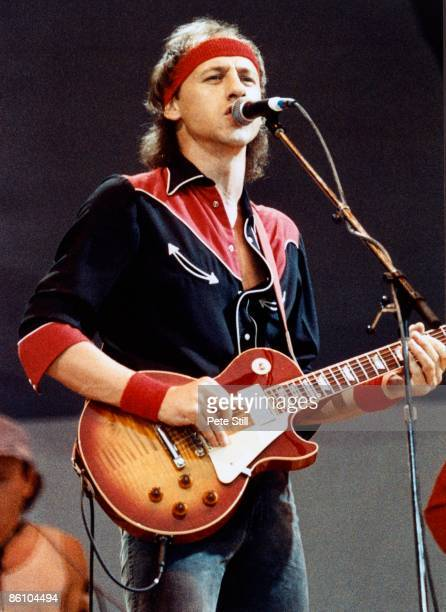 Photo of Mark KNOPFLER and LIVE AID and DIRE STRAITS Mark Knopfler performing live onstage at Live Aid playing Gibson Les Paul guitar wearing headband