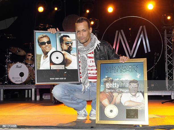 Photo of Mark MEDLOCK, posed with platinum record