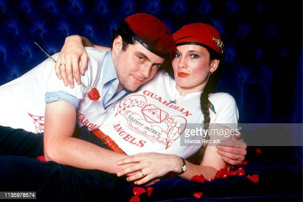 Photo of married American anticrime activists Curtis Sliwa and Lisa Evers both of the Guardian Angels as they embrace on a couch strwen with rose...