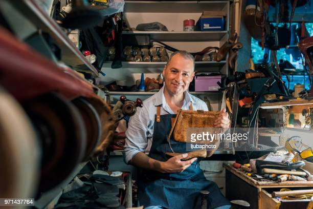 Photo of mature cheerful shoemaker in workshop holding shoes and bag. Looking at camera.