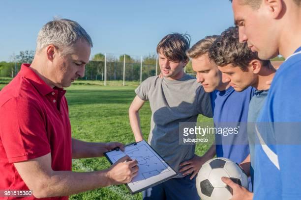 Foto von Reifen Trainer im Gespräch mit einer Gruppe von Fußball-Spieler