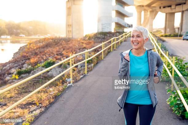 photo of mature woman running in the city - só uma mulher idosa imagens e fotografias de stock