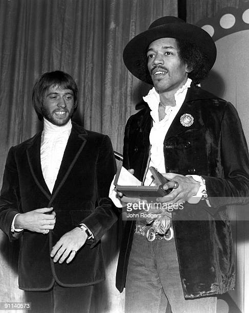 Photo of Maurice GIBB and Jimi HENDRIX receiving an award from Maurice Gibb