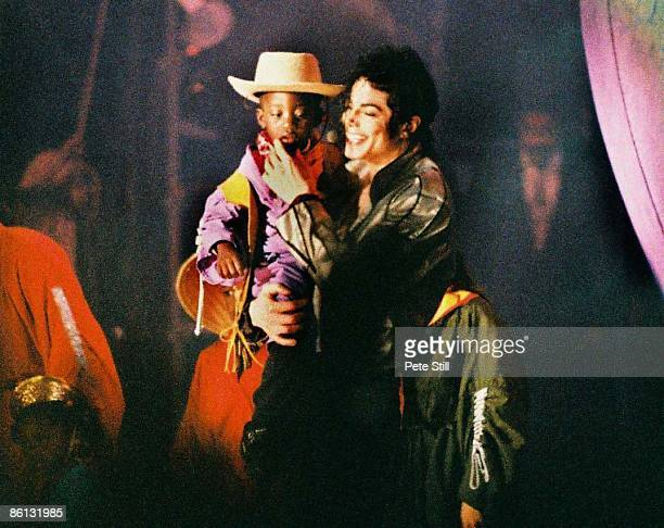 Photo of Michael JACKSON Michael Jackson performing on stage with child Dangerous Tour