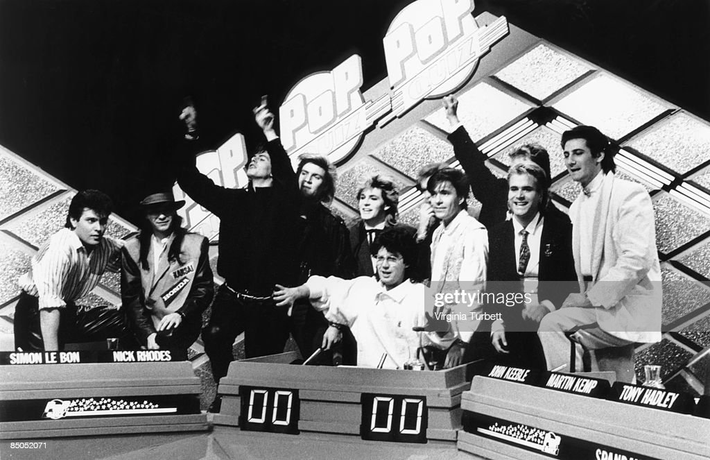 Photo of Mike READ and SPANDAU BALLET and DURAN DURAN; with Spandau Ballet - L-R: Roger Taylor, Andy Taylor, John Taylor, Simon Le Bon, Nick Rhodes, Mike Read (host), Martin Kemp, Steve Norman, Tony Hadley - recording Christmas Special of BBC 'Pop Quiz' TV show