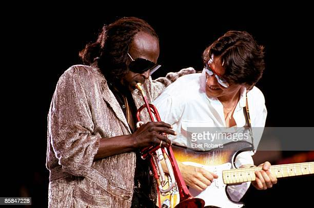 Photo of Miles DAVIS performing live onstage with guitarist Robben Ford at the Amnesty International Concert at Giant's Stadium in the Meadowlands...