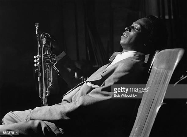 Photo of Miles DAVIS; posed, backstage, holding trumpet - at Shrine Auditorium, during Gene Norman's 'Just Jazz' Concert - -