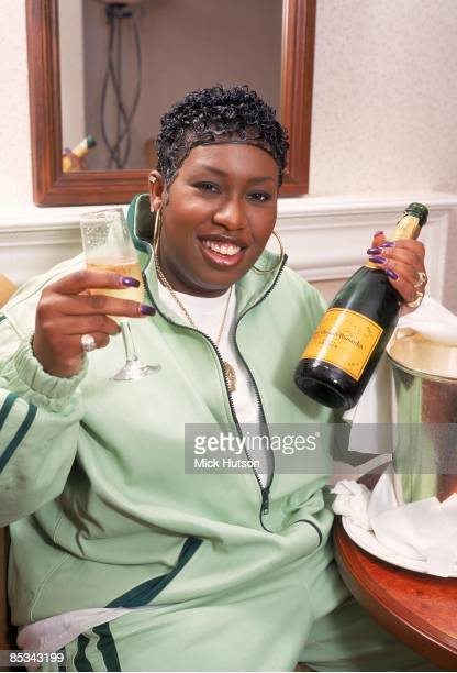 Photo of Missy ELLIOTT posed holding glass and bottle of champagne