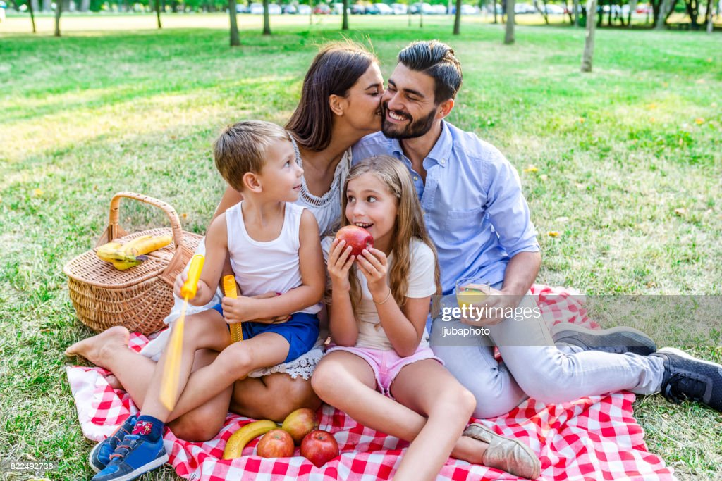 Photo of Mom kissing her husband in front of two kids in the nature : Stock Photo