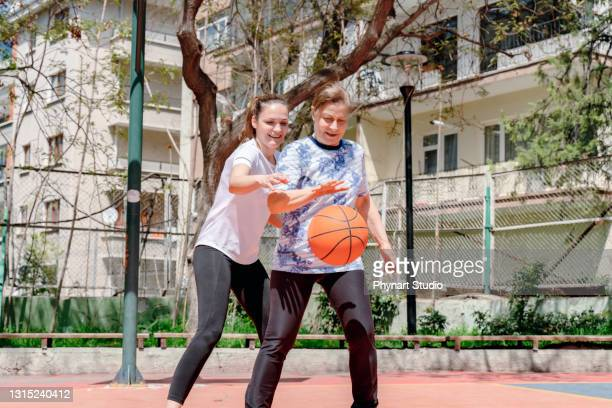 photo of mother with her daughter playing basketball outdoors - friendly match stock pictures, royalty-free photos & images
