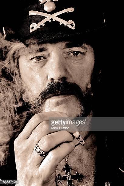 Photo of MOTORHEAD and LEMMY; of Motorhead, posed, studio, smoking cigarette