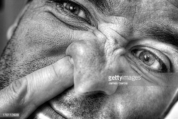 Photo of myself . Picking my nose. Taken in my house. Image is a black and white HDR. The photo shows a nose being picked and the face being wrinkled.