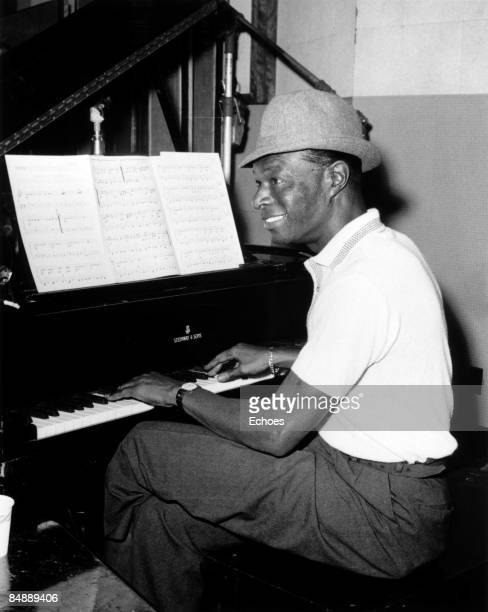 Photo of Nat King COLE Nat King Cole playing the piano in the recording studio