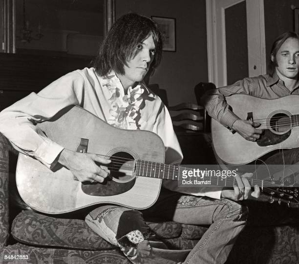 Photo of Neil YOUNG posed with Martin acoustic guitar