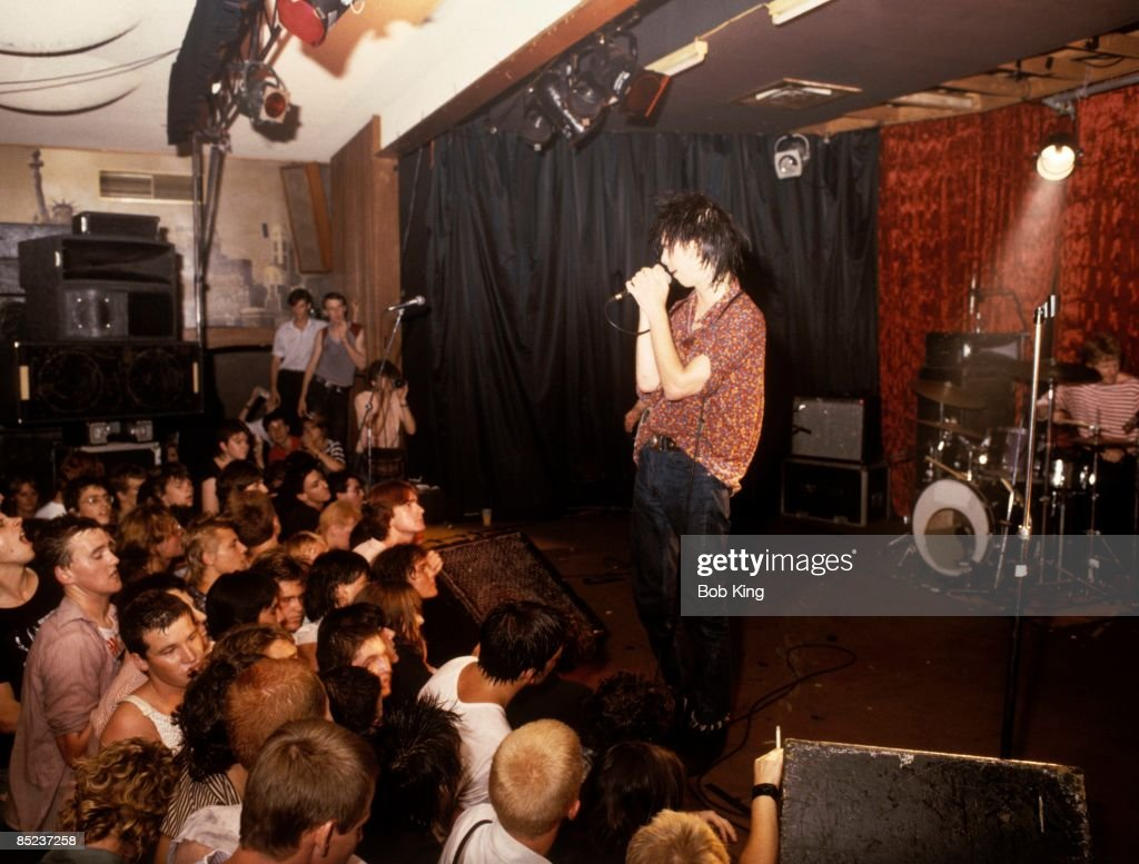 HOTEL Photo of Nick CAVE and BIRTHDAY PARTY, Nick Cave performing live onstage with front rows of audience in shot watching
