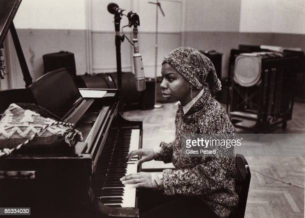 Photo of Nina SIMONE in the recording studio singing and playing piano