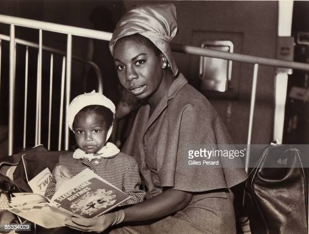Photo of Nina SIMONE posed at airport reading with child