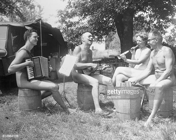Photo of nudists happily playing instruments while sitting on barrels at the colony is Roselawn Ind