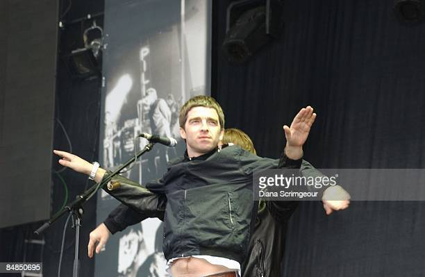 Photo of OASIS and Noel GALLAGHER Noel Gallagher with Liam Gallagher behind putting arms through his performing live onstage
