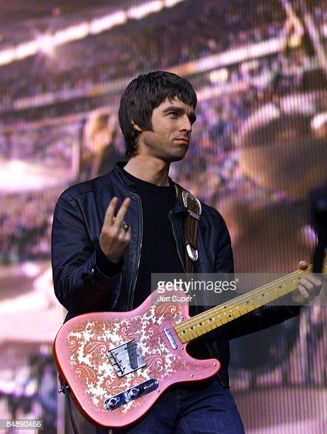 Photo of OASIS; Noel Gallagher performing live onstage at Reebok Stadium, flicking v's, swearing, gesticulating, playing paisley patterned Fender...