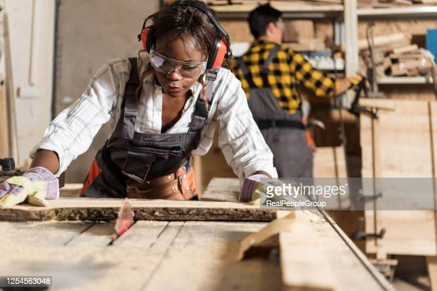 photo of one african-american female carpenter using circular - ear protection stock pictures, royalty-free photos & images