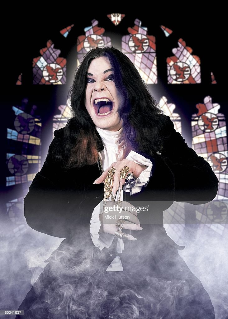 Photo of Ozzy OSBOURNE; posed, studio, with vampire teeth, in front of stained glass window