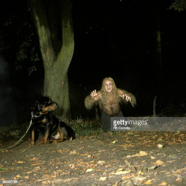 Photo of Ozzy OSBOURNE posed with dog in woods dressed as werewolf during 'Bark At The Moon' album cover shoot