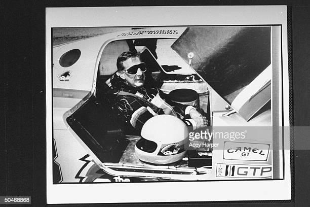 Photo of Panama's Gen Manuel Noriega's defense attorney Frank Rubino in race car during auto race1985